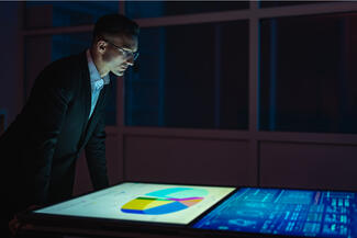A man in a suit looks down at graphs on a monitor