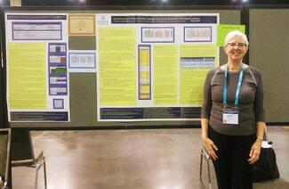Faculty member Luanne Andersson stands in front of her winning poster on Diagnostic Accuracy of Tests of Children's Language, Speech, Sound Development & Phonological Awareness