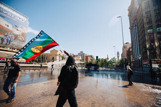A blue, green, red and yellow flag being waved by a person in a public square