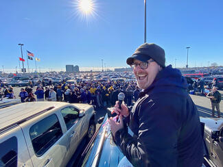 man with microphone in front of tailgate party