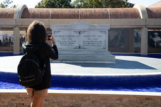 Student takes a photo of a memorial