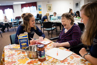 student working with resident at assisted living facility