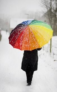 person with rainbow umbrella in snow