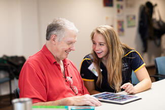 student helping an older person
