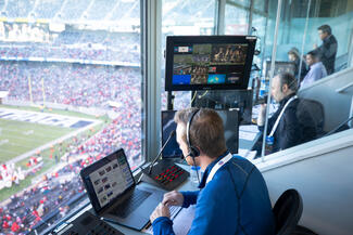 man watches football game from control room