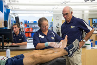 An athletic training student works on a person's ankle under the guidance of an instructor