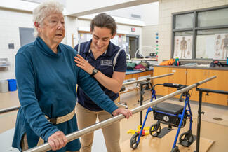 A student helps an older patient to walk in the physical therapy clinic