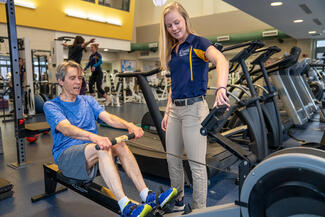 A Wellness Center member works out on a rowing machine under the guidance of a student trainer