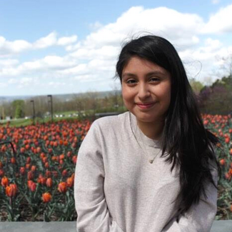 A young woman sitting in front of a bed of orange tulips. She is smiling at the camera. Behind her is a blue sky with fluffy while clouds. Her hair is dark, straight, and parted on the side.  She is wearing a beige sweater with a small necklace.