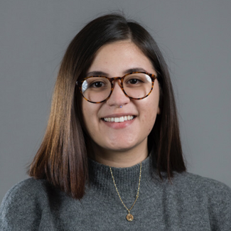 A young woman is wearing a grey sweater in front of a grey background.  She is smiling at the camera.  She wears tortoiseshell glasses and a gold necklace with her straight shoulder length hair parted slighted to the side.