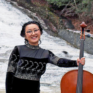 A young woman is standing in front of a waterfall smiling at the camera.  She is holding a cello.  She is wearing glasses and a dark velvet dress.
