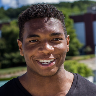 A young man is looking at the camera and smiling. He has short curly hair and is wearing a black shirt.  The background behind him is blurred and has buildings and trees in it.