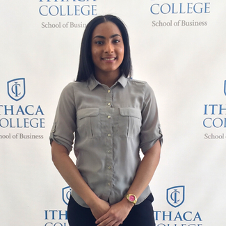 "A young woman stands in front of a white back ground with the words ""Ithaca College School of Business"" written all over.  She is smiling. Her straight dark hair is parted down the center and falls down her back. She is wearing a grey button up shirt, dark pants, and a gold watch with a red face."