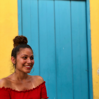 A young woman is looking off to the side and smiling. She is wearing a red off the shoulder blouse, her dark hair is pulled into a top knot on her head and she is wearing large thin hoop earrings.  Behind her is a light blue door on a bright yellow wall.