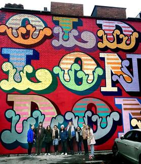 London Center students at Shoreditch in front of street art by Ben Eine.