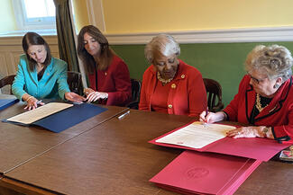 women in government signing official document