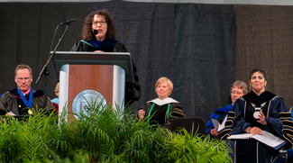 This is a photo of Linda Petrosino, Dean standing at a podium with other faculty members seated behind her. She is congratulating the new graduates.