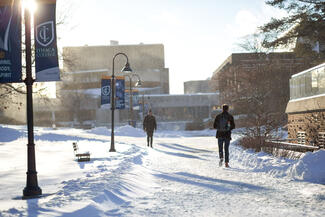 Students walking on snow-covered academic quad