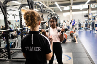 student lifts weights while a student trainer observes