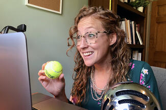 professor holds a tennis ball in front of a laptop