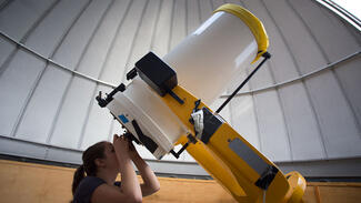 Amy Parker looks through the telescope at the Ford Observatory.