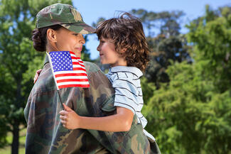 female soldier hugging boy holding US flag
