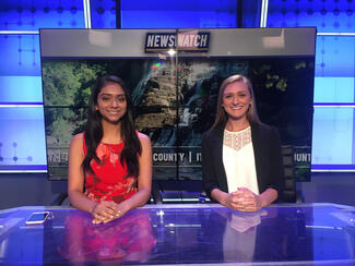 two students at the News Watch desk in the television studio