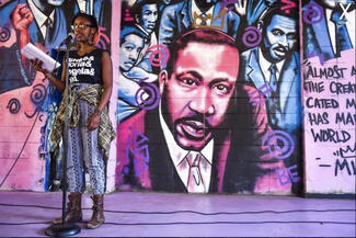 spoken word poet in front of a mural