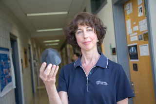 A woman holding a model asteroid