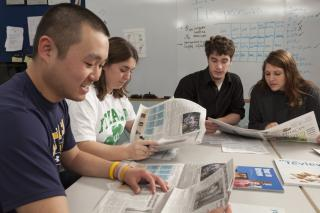 Students working on a newspaper assignment