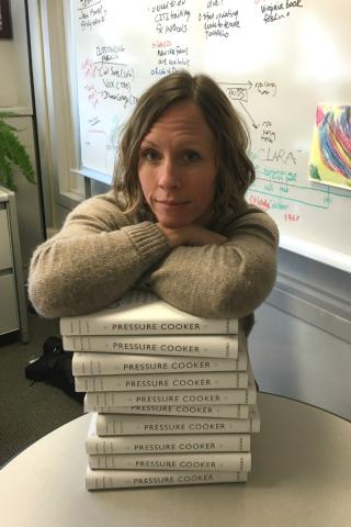 A woman leaning on a stack of books