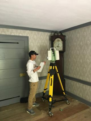 A man standing next to a 3D scanner inside a house
