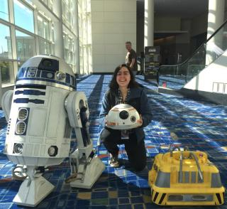 "A woman posing with two ""Star Wars"" droids"