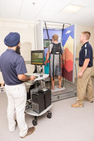 A student is in a harness attached to sensors. Another student in a blue shirt and tan pants is standing to the side observing. A faculty member is standing to the right using a computer to monitor activity.