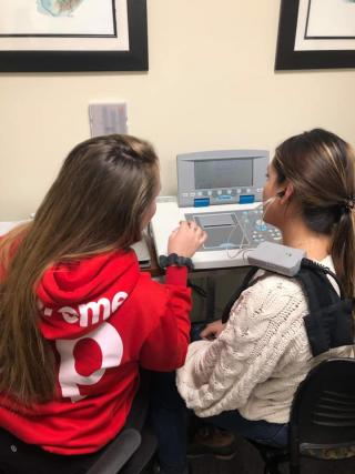 Two students have their backs to the camera. One is wearing a red shirt and the other a white shirt. They are using an audiology machine.