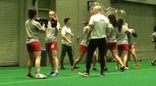 A student in a white shirt and black pants is training a group of female athletes in a gym. They are using hand-to-hand combat.