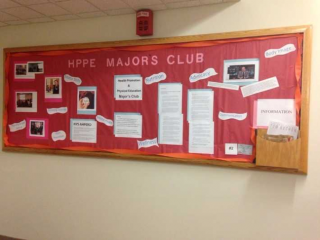 This is a bulletin board that has a red background and a variety of information on it about the HPPE majors club