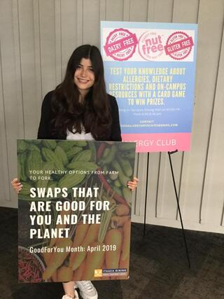 "A student is standing with a poster that says ""swaps that are good for you and the planet"""