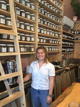 A student in a white shirt and blue pants is standing next to a ladder in front of an entire wall of herbs in jars.
