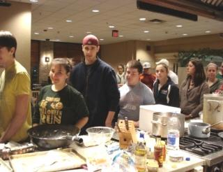 About 8 students are in a buffet line serving themselves food that they prepared as part of the nutrition club.