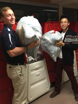 Two students in blue shirts and tan pants are holding large bags of clothes and getting ready to donate them.