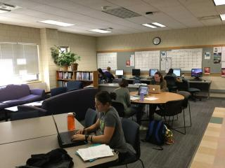 A picture of a large room with couches, work tables, and desktop computers. There are students scattered throughout the room studying.