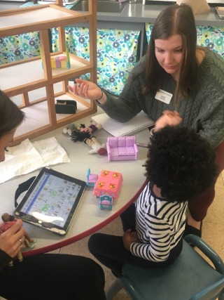 A student in a gray sweater is working with a child seated at a table. There is an ipad with information on it and the student is gesturing at the child encouraging them to communicate.