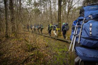 There are about 10 students wearing coats with camping backpacks on hiking through a forest.