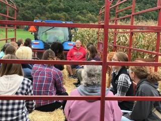 There is a large group of people seated on hay in a trailer in the back of a blue tractor about to go an a hay ride.