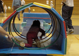 A young child is crawling through a colorful tunnel made of mats in a school gymnasium.