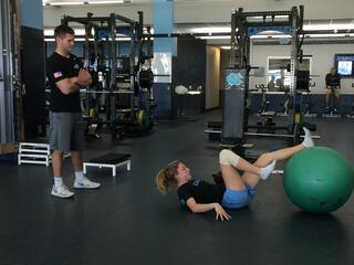 A student in a dark shirt and shorts is standing and observing an athlete on the floor doing exercises with a large green exercise ball.