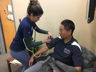 A student in a blue shirt is placing a blood pressure cuff on a man seated in a chair to take his blood pressure.