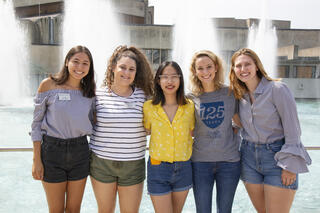 A group of students posing for a group shot in front of fountains