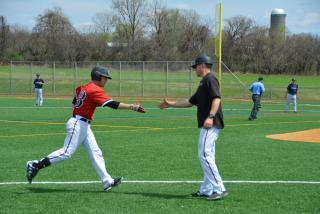A baseball coach congratulating a running player